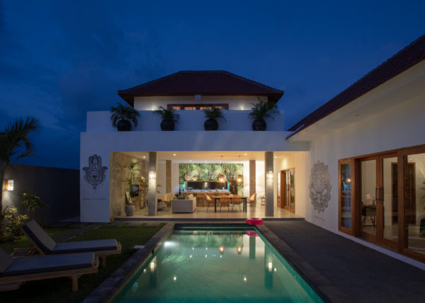 Villa ABSOLUTE – View from the pool of the living room, kitchen and dining room by nights